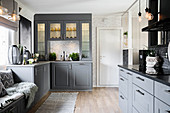 Open-plan country-house kitchen with grey cupboards and illuminated glass-fronted dresser