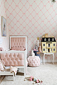 Bed, pouffe and dolls' house in girl's bedroom in pale pastel shades