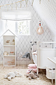 DIY dolls' house and white cot in bright room with diamond-patterned wallpaper