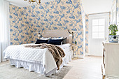 Double bed wiith headboard and chest of drawers in romantic bedroom with floral wallpaper