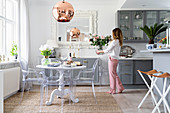 Open-plan kitchen with pale grey cupboards, round dining table and designer chairs - woman holding vase of roses
