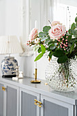 Bouquet of roses in glass vase, candlestick and table lamp on pale grey sideboard