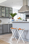 Pale grey counter and bar stools below extractor hood in open-plan kitchen