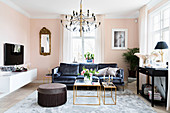 Dark velvet sofa, console table, pouffe, delicate coffee table and TV cabinet in pale pink living room