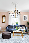 Dark velvet sofa, delicate coffee table and pouffe in pale pink living room