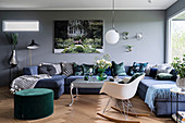 Blue sofa combination, green pouffe and classic rocking chair in living room with grey wall
