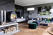 Large living room with grey walls, fireplace and firewood store, blue sofa combination and green pouffe