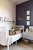 White child's bed and bedside cabinet in girl's bedroom with pink and purple wall