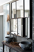 Vintage washstand with metal basins below mirrored cabinets in bathroom