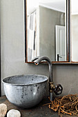 Vintage tap fitting and metal basin below mirrored cabinet in bathroom