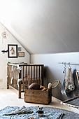 Cot against knee wall in vintage-style nursery