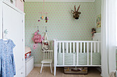 White cot, wardrobe and green wallpaper in nursery