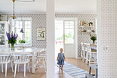 Little girl walking along runner between dining area with white furniture and kitchen