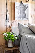 Elefantenbild an der Holzwand hinterm Bett, Flieder auf dem Nachttisch