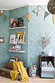 Bunting on wall with blue floral wallpaper in nursery
