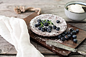 Chocolate torte with blueberries on wooden board