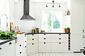 Light-flooded country-house kitchen decorated in white