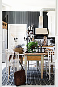 Three wooden tables in dining area of vintage-style country-house kitchen