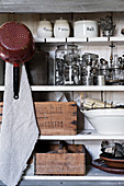 Kitchen utensils, cake tins and wooden crates on old shelving