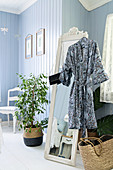 Kimono hung from free-standing mirror next to houseplant in bedroom with pale blue wall