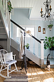 Rocking chair below staircase in foyer with wooden floor and pale blue wall