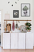Row of hooks above vintage accessories on white sideboard