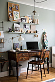 Antique, dark wood desk below shelves on grey wall