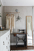 Old treadle sewing machine below suspended branch used as clothes rack