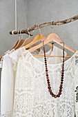 Cream lace blouses hung from suspended branch used as clothes rack