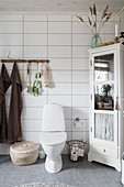 Toilet in bathroom with horizontal rectangular tiles and Bohemian accessories