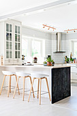 Barstools at kitchen counter with chalkboard end panel in open-plan kitchen