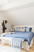 Bed below sloping ceiling in blue-and-white bedroom