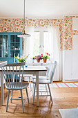 Spoke-back chairs around table in dining room with floral wallpaper