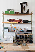 Vintage accessories and decorative letter on shelves above sewing table