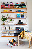 Books arranged by colour on wall-mounted designer shelves