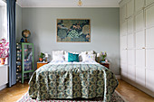 Double bed and floor-to-ceiling fitted wardrobes in bedroom in shades of blue and green