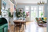 Wohnraum in Altbauwohnung mit Esstisch vor Bilderwand mit Durchgang