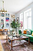 Grünes Sofa und Glas-Couchtisch in Altbauwohnung, im Hintergrund Esstisch vor Bilderwand