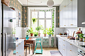 White cupboards and dark green patterned wallpaper in light-flooded kitchen