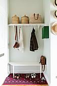 Vintage-style cloakroom in niche with coat pegs below shelf