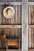 Folding chair below straw hat hung on rustic wooden wall