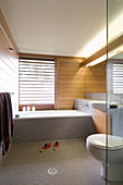 Grey mosaic tiles and wood panelling in minimalist bathroom