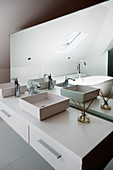 Twin countertop sinks on washstand and mirrored partition wall in designer bathroom