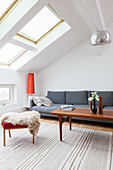 Grey sofa, coffee table and fur blanket on stool in attic living room