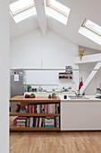 Island counter running into shelves in white kitchen with skylights