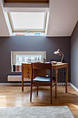 Desk and chair in attic study with grey walls