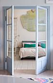 Open double doors with view into bedroom with board floor