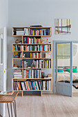 Modern bookcase next to double doors leading into bedroom