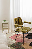 Chair with leaf-patterned upholstery on herringbone rug