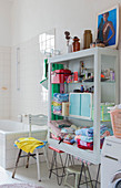Open-fronted cupboard on two retro stools used as shelves in bathroom